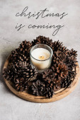 Photo Scented candle with pine cones on wooden plate near christmas in coming lettering on grey background