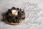 Illatos gyertya fenyőtobozokkal fából készült tányéron közel boldog karácsonyt és boldog új évet felirat szürke háttér