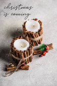 Scented candles decorated with cinnamon sticks near christmas is coming lettering on textured grey background