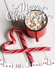 Červený šálek kakaa v blízkosti vánoční cukroví hole v blízkosti veselých vánočních nápisů na dřevěném pozadí