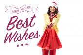 radostná mladá žena v santa klobouku a šála s ornamentem drží červené nákupní tašky v blízkosti veselých Vánoc, nejlepší přání nápisy na bílém