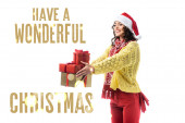 joyful young woman in santa hat, scarf and knitted sweater holding gifts near have a wonderful christmas lettering on white