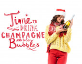joyful young woman in santa hat looking at bottle of champagne near time to drink champagne and blow bubbles lettering on white