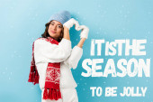 pleased young woman in warm scarf, gloves and hat showing heart sign near it is the season to be jolly lettering on blue