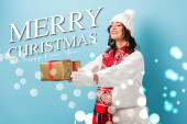 mladá potěšená žena v zimním oblečení s natažené ruce drží zabalený dárek v blízkosti veselých Vánoc a šťastný nový rok nápis na modré
