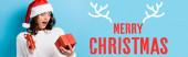 mladá šokovaná žena při pohledu na dárkové krabice v blízkosti veselých vánočních nápisů na modré, prapor