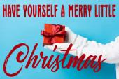 abgeschnittene Ansicht einer jungen Frau in Handschuhen mit Geschenkschachtel in der Nähe haben Sie selbst einen fröhlichen kleinen Weihnachtsschriftzug auf blau