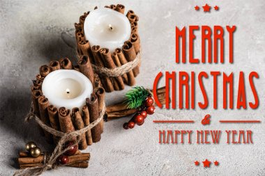 Scented candles decorated with cinnamon sticks near merry christmas and happy new year lettering on textured grey background stock vector