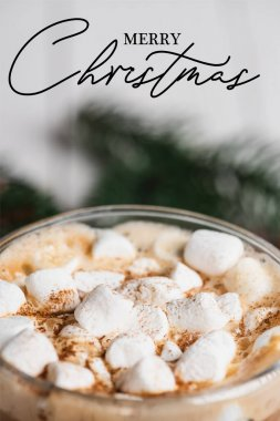 Close up view of glass cup of cocoa with marshmallows and cinnamon near merry christmas lettering stock vector