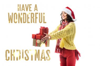 Joyful young woman in santa hat, scarf and knitted sweater holding gifts near have a wonderful christmas lettering on white stock vector