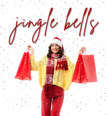 Pleased woman in santa hat and scarf with ornament holding red shopping bags near jingle bells lettering on white stock vector