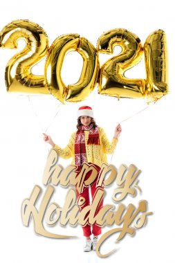 Young woman in santa hat and scarf holding balloons with 2021 numbers near happy holidays lettering on white stock vector