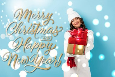 Young joyful woman in winter outfit holding wrapped presents near merry christmas and happy new year lettering on blue stock vector