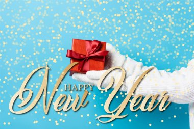 Cropped view of young woman in gloves holding gift box near happy new year lettering on blue stock vector