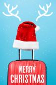 červená santa klobouk na moderní cestovní taška s veselými vánočními nápisy v blízkosti jelení rohy ilustrace na modré