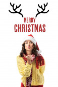 mladá žena v santa klobouk a šála posílání vzduchu polibek v blízkosti veselých vánočních písmen a jelení rohy ilustrace na bílém