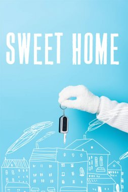 Cropped view of woman in white glove holding key near sweet home lettering and houses illustration on blue stock vector
