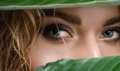 detailní záběr blondýny s mokrými vlasy a zelenými listy