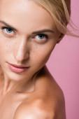 krásná blondýnka s pihami a holými rameny izolované na růžové