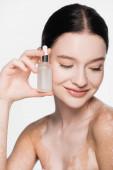 lächelnde junge schöne Frau mit Vitiligo hält Serum isoliert auf weiß