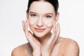 usmívající se mladá krásná žena s vitiligem a obličejovým krémem na tvářích izolovaných na bílém