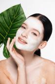 fiatal gyönyörű nő vitiligo és agyag maszk az arcon homályos levél a háttérben elszigetelt fehér