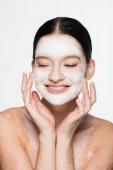 lächelnde junge schöne Frau mit Vitiligo und Tonmaske auf dem Gesicht isoliert auf weiß