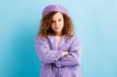 skeptische junge Frau steht mit verschränkten Armen auf blauem Grund
