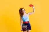 happy young woman in summer outfit holding paper plane on yellow