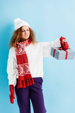 dissatisfied woman in hat and mittens holding wrapped gift box on blue