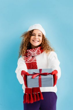 Cheerful woman in hat and mittens with outstretched hands holding wrapped gift box on blue stock vector