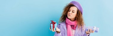 Curly woman in winter coat, beret and pink knitted scarf choosing between christmas presents on blue, banner stock vector