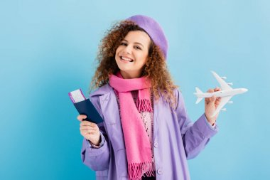Positive woman in beret, scarf and coat holding passport and toy plane on blue stock vector