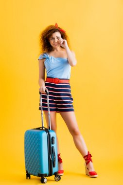 Full length of sad woman in summer outfit and wedge sandals standing near suitcase and crying on yellow stock vector