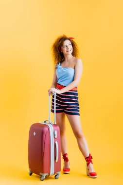 Full length of happy woman in summer outfit and wedge sandals standing near suitcase on yellow stock vector