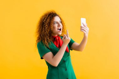 Rude young woman showing middle finger while taking selfie on yellow stock vector