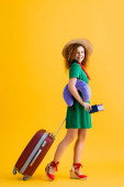 full length of happy woman in straw hat holding passport, travel pillow and walking with luggage on yellow
