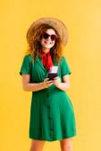 boldog nő szalma kalap, napszemüveg és ruha gazdaság útlevél sárga