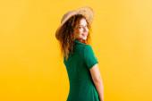 šťastná mladá žena v slamáku a zelené šaty izolované na žluté