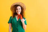 happy young woman in straw hat and green dress pointing with thumb isolated on yellow
