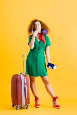 Full length of sleepy tourist in green dress with travel pillow holding passport and yawning near suitcase on yellow stock vector