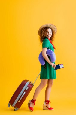 Full length of happy woman in straw hat holding passport, travel pillow and walking with luggage on yellow stock vector