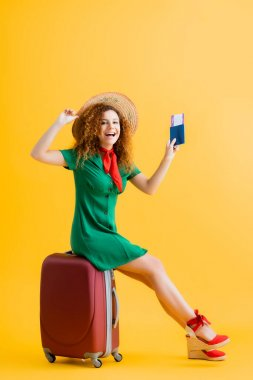 Full length of happy woman in straw hat holding passport and sitting on red luggage on yellow stock vector