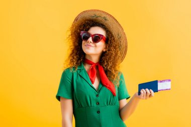Cheerful woman in straw hat, sunglasses and dress holding passport on yellow stock vector