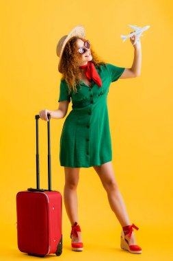 Full length of cheerful woman in straw hat, sunglasses and dress holding toy plane near luggage on yellow stock vector