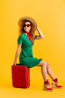 Full length of smiling woman in straw hat, sunglasses and dress sitting on luggage on yellow stock vector