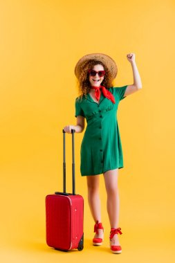 Full length of excited woman in straw hat, sunglasses and dress standing with luggage on yellow stock vector