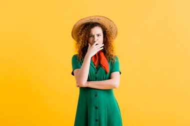 Scared young woman in straw hat and green dress covering mouth on yellow stock vector