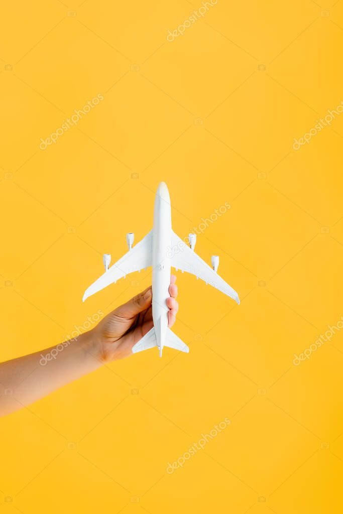 Cropped view of woman holding toy airplane isolated on yellow stock vector