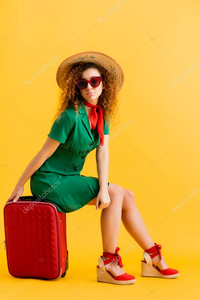Full length of sad woman in straw hat, sunglasses and dress sitting on luggage on yellow stock vector